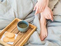 Kaffe i underlag den välformade kvinnlign lägger benen på ryggen i varma sockor, trämagasinet för frukost i säng två koppar kaffe Royaltyfri Fotografi