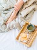 Kaffe i underlag den välformade kvinnlign lägger benen på ryggen i varma sockor, trämagasinet för frukost i säng två koppar kaffe Arkivbilder