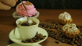 Kaffe i vita koppar, kakor och en spridning av kaffebönor på tabellen stock video