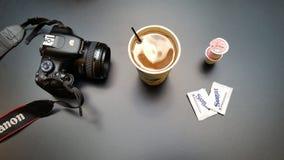 Kaffe, kräm och kamera Arkivfoton