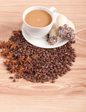 Kaffe kuper, anise på kaffebönor, sötsaker på träbakgrunden Arkivfoton