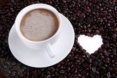 Kaffe kuper med bönor, och hjärta formar Arkivfoton