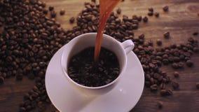 Kaffe kuper och kaffebönor arkivfilmer
