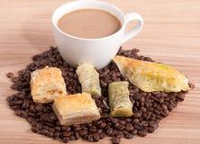 Kaffe kuper och kaffebönor, sötsaker på träbakgrunden Arkivfoto