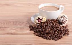 Kaffe kuper och kaffebönor, sötsaker på träbakgrunden Fotografering för Bildbyråer
