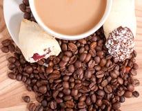 Kaffe kuper och kaffebönor, sötsaker på träbakgrunden Arkivbild