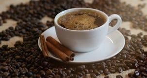 Kaffe kuper och kaffeb?nor En vit kopp av avdunstande kaffe p? tabellen med den grillade b?nan Materiell?ngd i fot r?knat 4K lager videofilmer