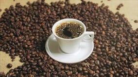 Kaffe kuper och kaffeb?nor Vit kopp av avdunstande kaffe p? tabellen med den grillade b?nan Materiell?ngd i fot r?knat arkivfilmer