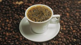Kaffe kuper och kaffeb?nor Vit kopp av avdunstande kaffe p? tabellen med den grillade b?nan Materiell?ngd i fot r?knat lager videofilmer