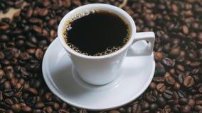 Kaffe kuper och kaffeb?nor Vit kopp av avdunstande kaffe p? tabellen med den grillade b?nan Materiell?ngd i fot r?knat stock video