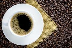Kaffe kuper på kaffebönabakgrund Arkivfoton