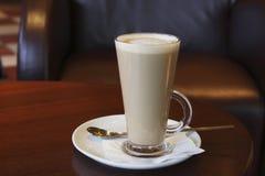 Kaffe - Latte Cappuccino i ett högväxt exponeringsglas fotografering för bildbyråer