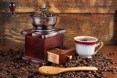 Kaffe maler molar och koppen kaffe och träskeden på gammal retro bakgrund med grillade bönor Arkivbilder