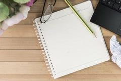 Kaffe med anteckningsboken, blomma, blyertspenna, ögonexponeringsglas på wood backgroun Arkivbild