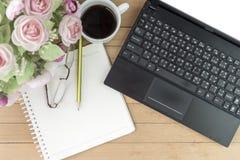 Kaffe med anteckningsboken, blomma, blyertspenna, ögonexponeringsglas på wood backgroun Royaltyfri Foto