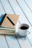 Kaffe med böcker och blyertspennan på trägolv för himmelblått Arkivbilder