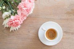 Kaffe med blommor på trätabellen fotografering för bildbyråer