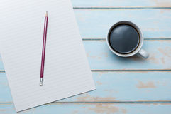 Kaffe med brevpapper och blyertspenna på färgträgolv Royaltyfri Foto