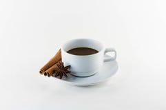 Kaffe med den kanelbruna pinnen och stjärnaanis som isoleras på vit arkivfoto
