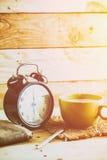 Kaffe med den retro klockan på wood tabellbakgrund Arkivbild