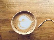 Kaffe med en kabel för hörlurar på en trätabell royaltyfri bild