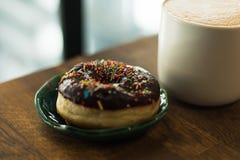Kaffe med en utdragen hj?rta och att mj?lka p? en tr?tabell i en coffee shop royaltyfria bilder