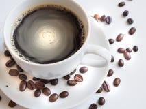 Kaffe med en vit kopp och bruna på ett tefat Arkivfoton