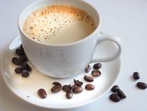 Kaffe med en vit kopp och bruna på ett tefat Royaltyfri Bild