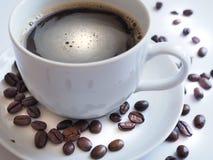 Kaffe med en vit kopp och bruna på ett tefat Royaltyfria Foton