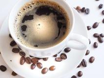 Kaffe med en vit kopp och bruna på ett tefat Arkivfoto