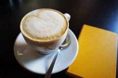 Kaffe med ett skum i form av hjärta arkivfoto