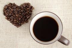 Kaffe med hjärtaformbönor arkivfoton