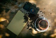 Kaffe med kameran och boken Arkivbild