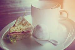 Kaffe med klimpar i kokosnötkräm och smörgåsBolognakorv Arkivfoto