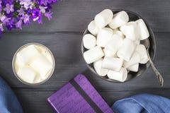 Kaffe med marshmallower och anteckningsboken på träbakgrund Royaltyfri Foto