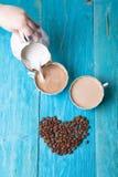 Kaffe med mjölkar, häller mjölkar från mjölkbudet, blå träbakgrund royaltyfria foton