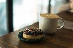 Kaffe med mjölkar och en munk arkivbild