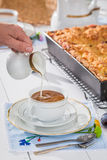 Kaffe med mjölkar och plommonkakan i sommar arkivbilder
