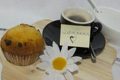 Kaffe med muffin på vit bakgrund med behagfull handstil och fotografering för bildbyråer
