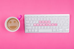 Kaffe med smileyframsidan och den bra morgonen smsar på tangentbordet Royaltyfri Fotografi