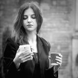 kaffe mer tid Telefon för innehav för affärskvinna och tycka omkaffe I royaltyfri foto