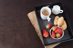 Kaffe, mini- franska bakelser och jordgubbar på trämagasinet över den svarta tabellen Svart bakgrund arkivbilder