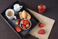Kaffe, mini- franska bakelser och jordgubbar på trämagasinet över den svarta tabellen Svart bakgrund arkivfoton