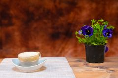 Kaffe mjölkar och kakor på brun bakgrund arkivbilder