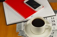 Kaffe, mobiltelefon, dagbok och min röda anteckningsbok på skrivbordet Utrymme för text Royaltyfria Foton