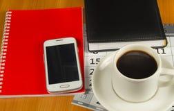 Kaffe, mobiltelefon, dagbok och min röda anteckningsbok på skrivbordet Utrymme för text Arkivbild