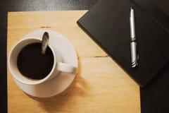 Kaffe och anteckningsbok på tabellen Royaltyfri Bild