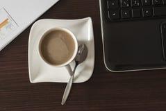Kaffe och bärbar dator Arkivbild