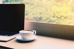 Kaffe och bärbar dator på skrivbordstång i kafé med drinken i morgon Arkivfoto