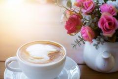 Kaffe och blomma på den wood tabellen Arkivfoto